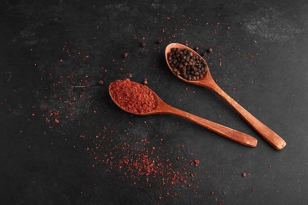 Paprika en zwarte peper in houten lepels.