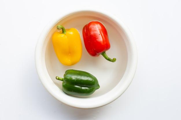 Paprika gedrenkt in water. verse groenten wassen op wit