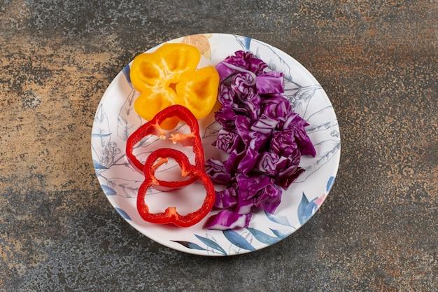 Paprika's en fijngehakte rode kool, op het marmeren oppervlak