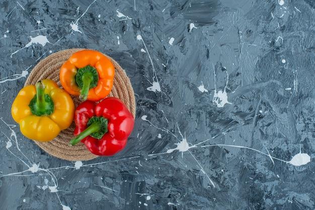 Paprika's op een onderzetter op het marmeren oppervlak