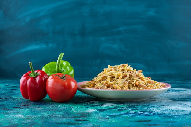 Paprika's, tomaten en noedels in een bord, op de blauwe tafel.