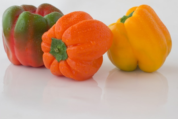 Paprika's van verschillende kleuren met waterdruppeltjes op een wit