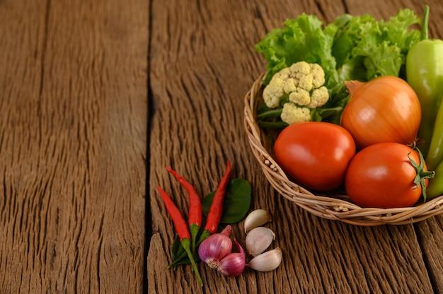 Paprika, tomaat, ui, salade, chili, sjalot, knoflook, bloemkool en kaffir limoenblaadjes op een houten mandje op houten tafel
