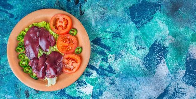 Paprika, tomaten, sla en kippenafval op een kleiplaat