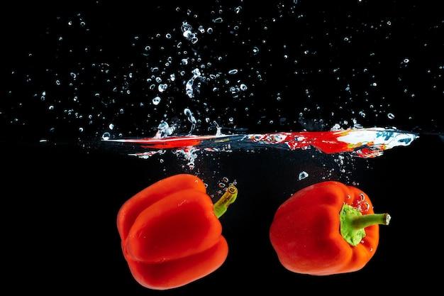 Paprika valt in het water met een plons tegen zwart
