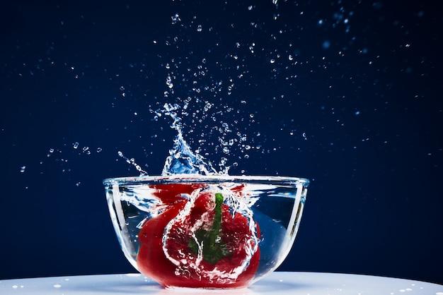 Paprika valt naar beneden in glazen water splash.