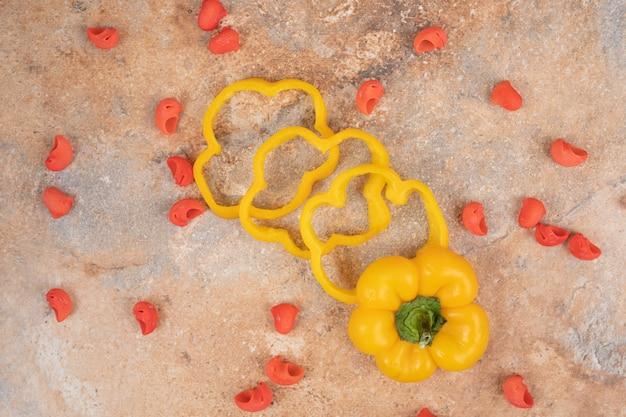 Paprikaplakken en rode deegwaren op oranje achtergrond