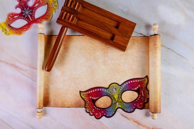 Papyrusrol met purim-maskers en lawaaimaker voor fastival.
