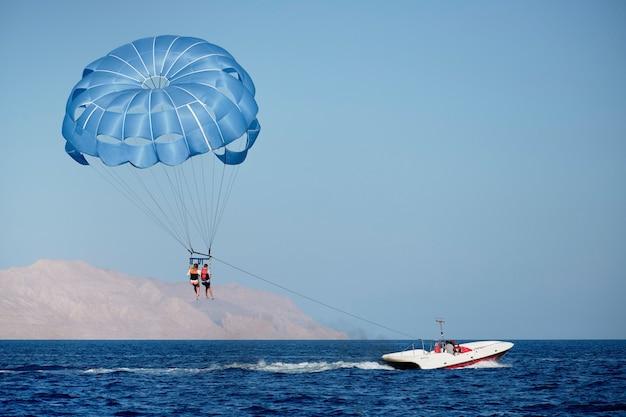 Parachutevlucht over het water tegen de achtergrond van bergen.