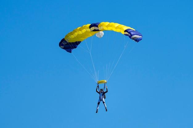 Parachutist met gele en blauwe parachute tegen een blauwe lucht