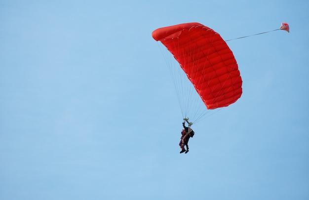 Parachutisteninstructeur met leerling in de lucht