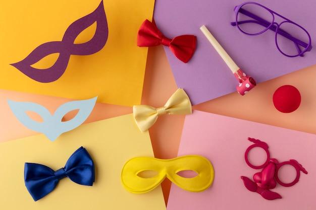 Parademasker en accessoires op verschillende kleuren papier