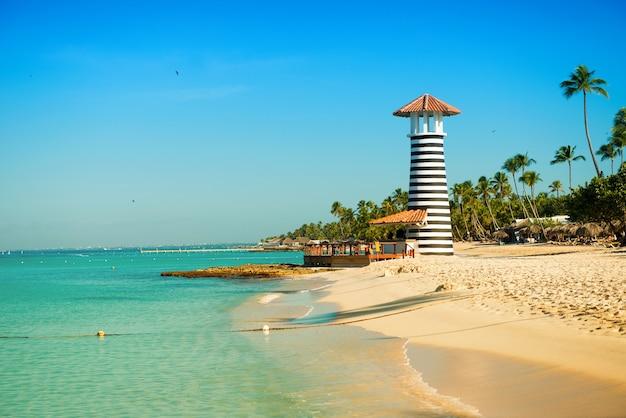 Paradijs caribisch landschap. heldere zee, wit zand, tropische palmbomen en vuurtoren aan zandstrand