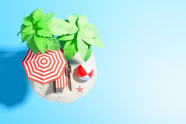Paradijseiland in de oceaan, bovenaanzicht. chaise longue, paraplu en bal onder palmbomen op het zand.