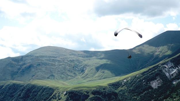 Paraglider die tijdens de zomerdag over bergen vliegt - georgië, kazbegi