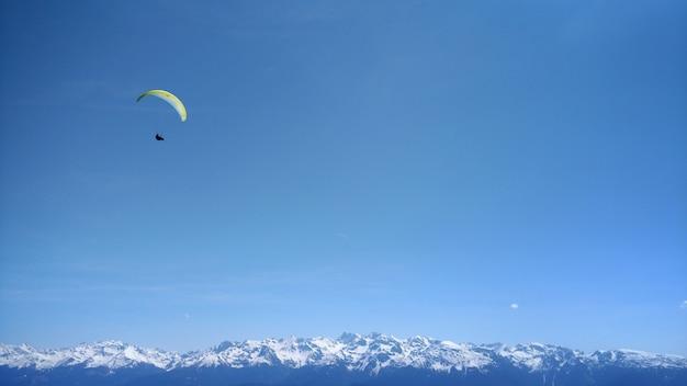 Paraglider in de blauwe lucht van de bergen