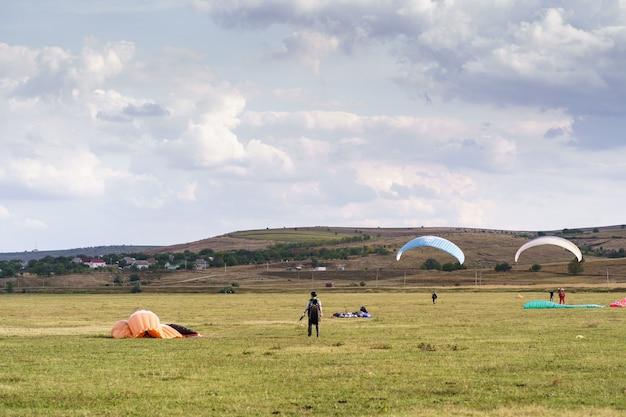 Paragliders silhouet vliegen over prachtig groen landschap onder blauwe hemel met wolken.