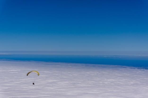 Paragliding over een zee van wolken in de lucht in een heldere zonnige dag