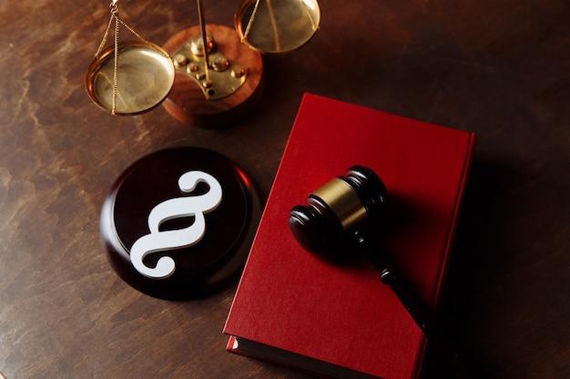 Paragraaf symbool in rechtszaal en rechter hamer op een wetboek.