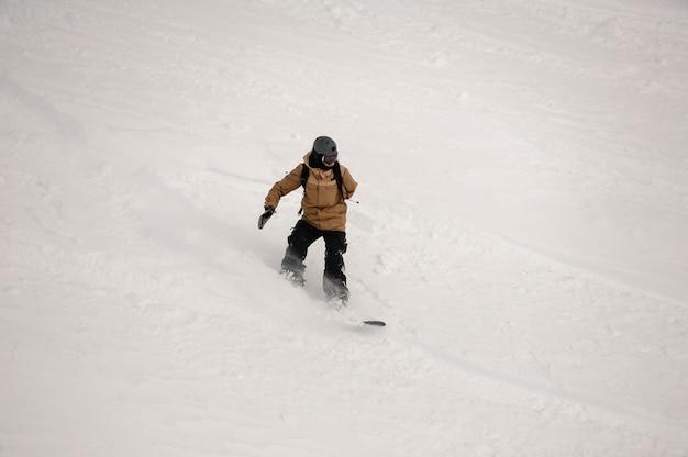 Paralympische snowboarder die langs de met sneeuw bedekte heuvel in het populaire toeristenoord gudauri in georgië rijdt