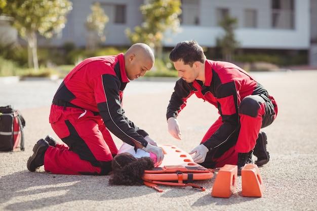 Paramedici die gewond meisje op een bord zetten
