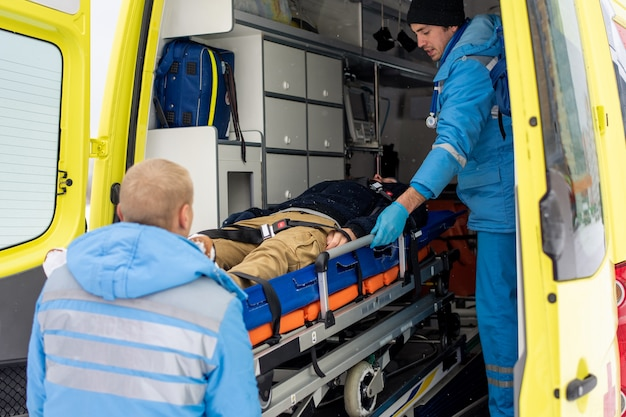 Paramedici in uniform duwen brancard met vaste bewusteloze man in ambulanceauto om hem naar het ziekenhuis te brengen