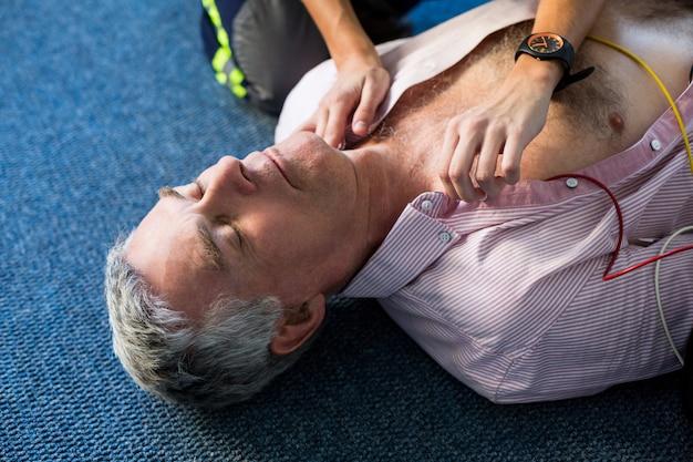 Paramedicus die een externe defibrillator gebruikt tijdens cardiopulmonale reanimatie