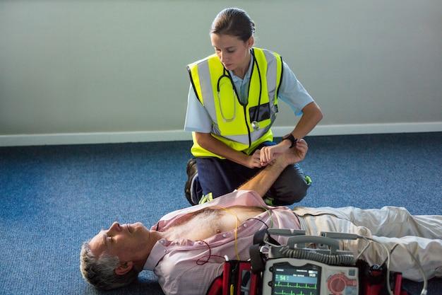Paramedicus die een patiënt onderzoekt tijdens cardiopulmonale reanimatie