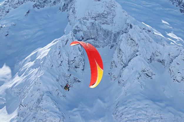 Paraplane vliegt over de besneeuwde bergen van de kaukasus en zonnige blauwe lucht