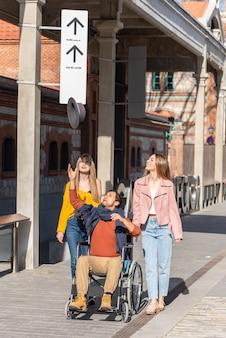 Paraplegische jonge latijns-amerikaanse man in een rolstoel naast twee gelukkige jonge blanke meisjes die een hoed in de lucht gooien terwijl ze door de straat wandelen