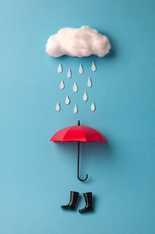 Paraplu en regenlaarzen onder de wolk op hemelsblauw