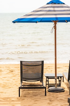 Paraplu en stoel rond strandoverzees met blauwe hemel
