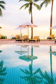 Paraplu en stoel rond zwembad in hoteltoevlucht met zonsopgang in ochtend