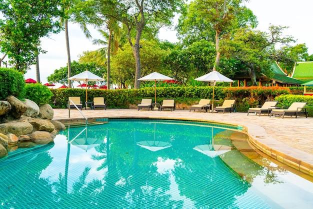 Paraplu en stoel rond zwembad in resorthotel voor vakantiereizen en vakantie in de buurt van zee oceaanstrand bij zonsondergang of zonsopgang