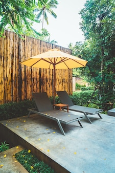 Paraplu en zwembadbeddecoratie rond zwembad in hotelresort Premium Foto