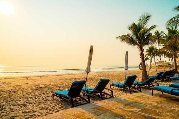 Paraplu stoel strand met palmboom en zee strand bij zonsopgang tijden, vakantie en vakantie concept