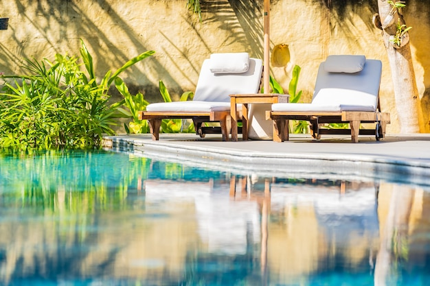 Parasol en stoel rond buitenzwembad in resorthotel voor vrije tijd op vakantie