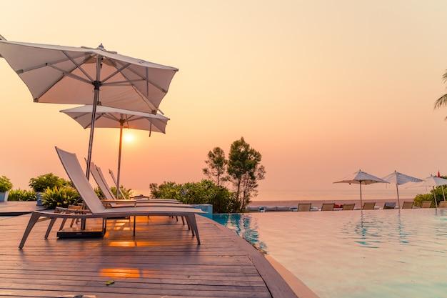 Parasol en stoel rond zwembad met uitzicht op zee oceaan
