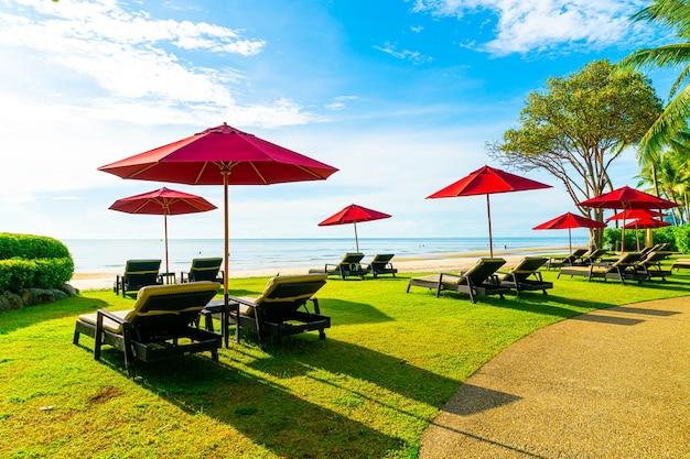 Parasol en strandstoel met zee strand en blauwe lucht