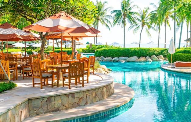 Parasol met terrasstoel en tafel rondom het zwembad