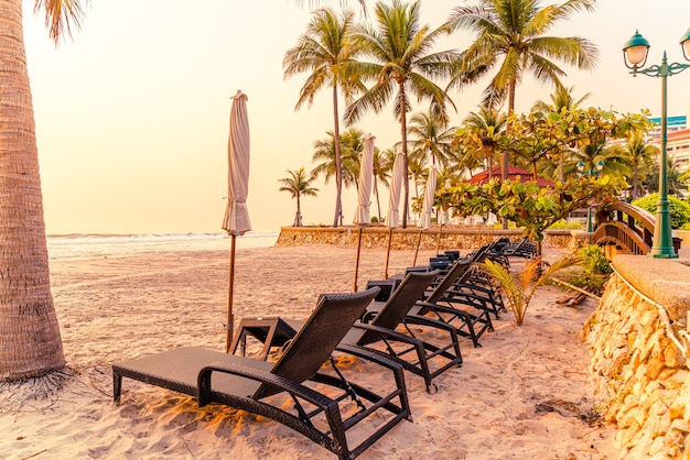 Parasol stoel strand met palmboom en zee strand bij zonsopgang - vakantie en vakantie concept