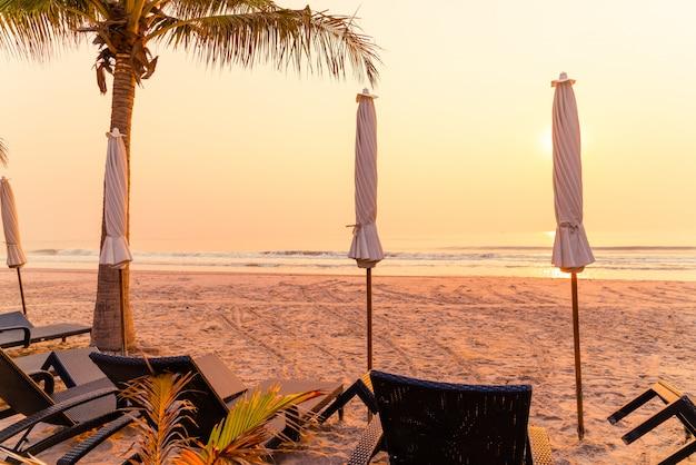Parasols en bureaustoelen op het strand met palmboom