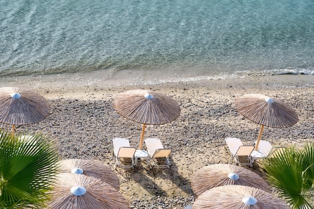 Parasols en ligbedden op het strand van fourka scala in halkidiki, griekenland