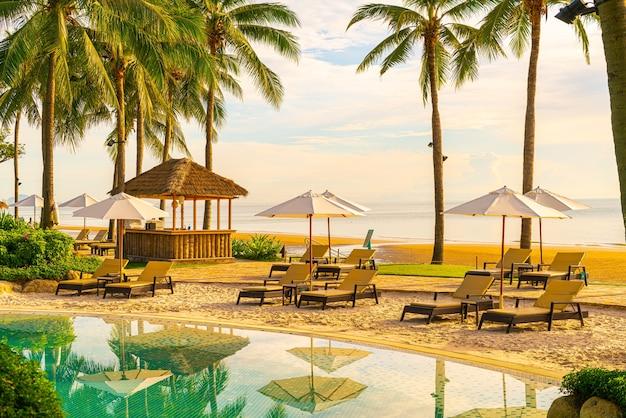 Parasols en ligstoelen rond zwembad vlakbij het strand