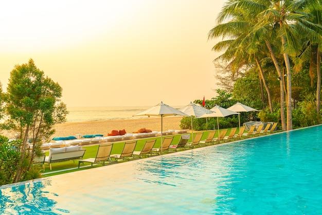 Parasols en stoelen rondom zwembad met uitzicht op zee