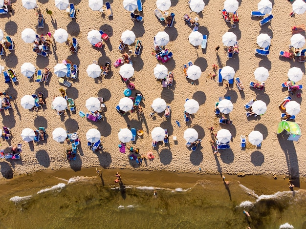 Parasols, ligbedden op zandstrand, drone luchtfoto van bovenaf