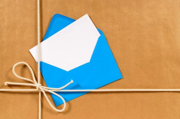 Parcel met blauwe envelop en leeg bericht kaart
