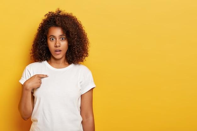 Pardon? verontwaardigde afro-amerikaanse dame voelt zich perplex, wijst naar zichzelf, opgeschrikt door aanstootgevende woorden, kijkt verwarrend, draagt witte kleren, staat tegen gele muur, lege ruimte opzij
