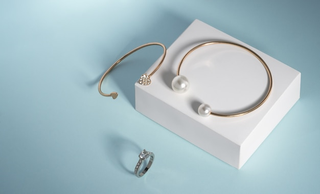 Parel- en diamanten gouden armbanden en witgouden ring op witte doos op blauw met kopieerruimte