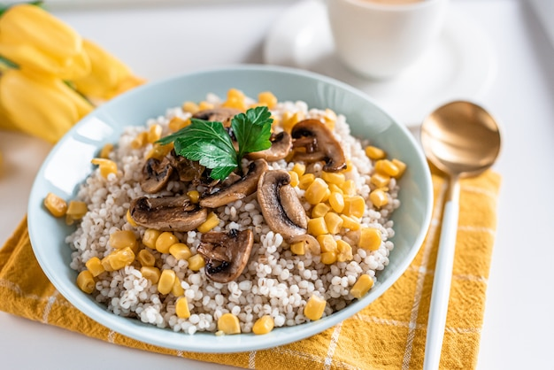 Parelgort met champignons en maïs, gezond voedselconcept, ontbijt, kop met zwarte koffie